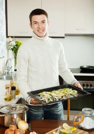 roasting pan: Smiling guy cooking trout fish in roasting pan at  kitchen