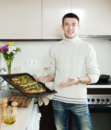 guy with cooked fish on  frying pan at  kitchen photo