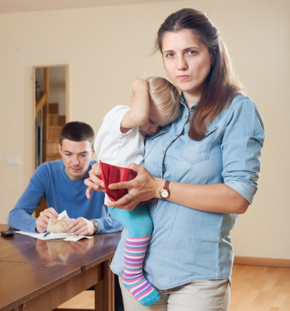 frugality: Financial problems in family. Sad woman wit baby against husband with money