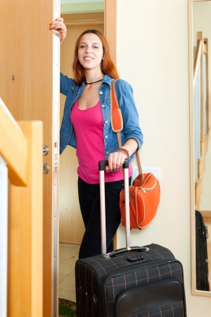 Positive woman with suitcase near door in hall at home photo