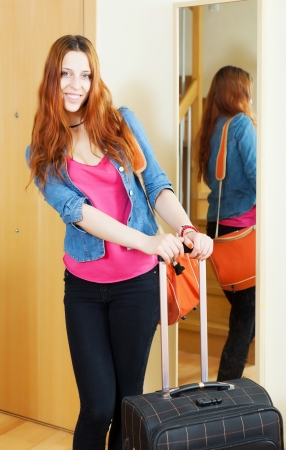 Cheeful red-haired woman with suitcase near door at home photo
