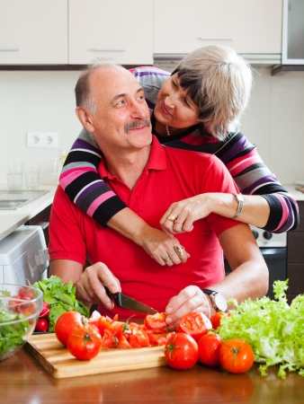 Loving mature couple cooking  together in  kitchen photo