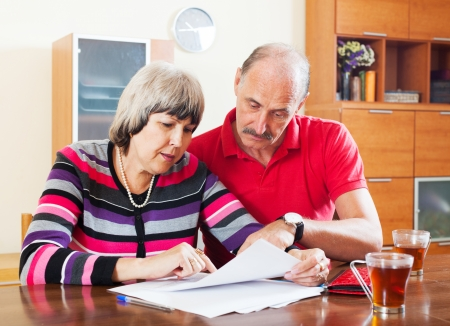wistful: serious mature couple reading financial document together