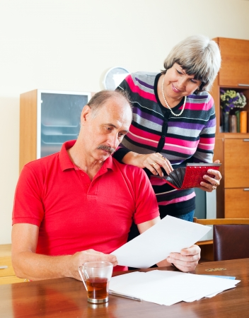 50 something:  senior family  with financial documents at home interior Stock Photo