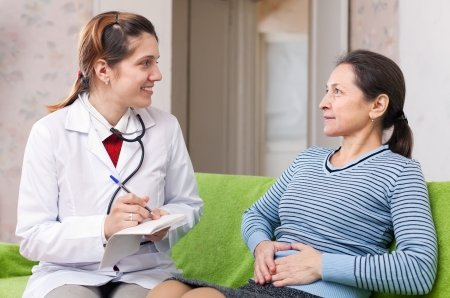 Mature woman complaining  to doctor about stomachache at  hospital photo