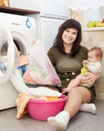 Young housewife with little baby putting clothes in to washing machine and smiling in kitchen photo