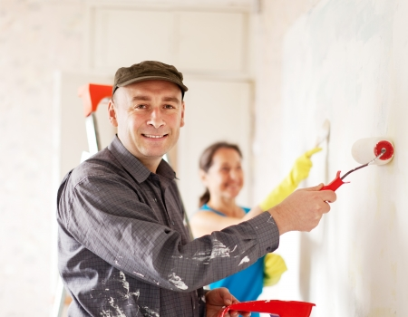 Man and woma paints wall at house together photo