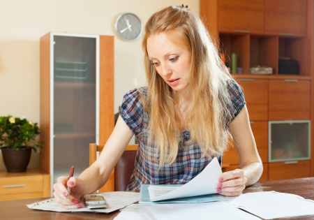 utility payments: serious blonde woman fills in documents at home