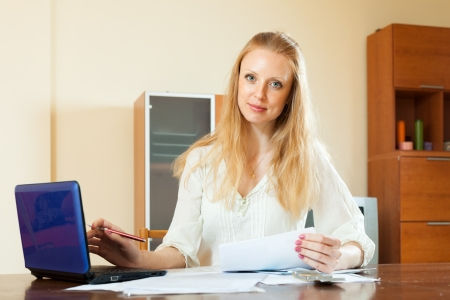 wistful: wistful blonde woman working with financial documents and laptop at home