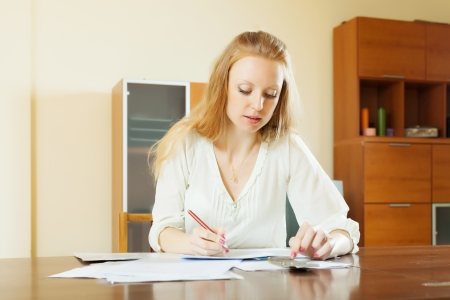 serious woman fills in financial documents at table in home interior photo
