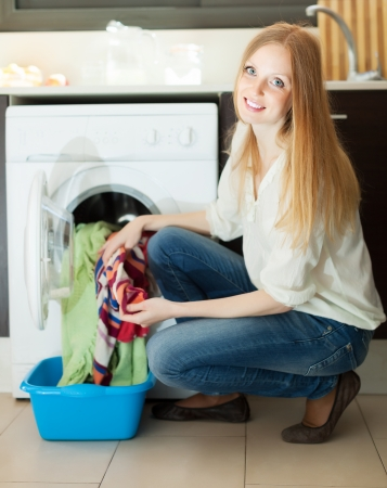 blonde woman using washing machine at home photo