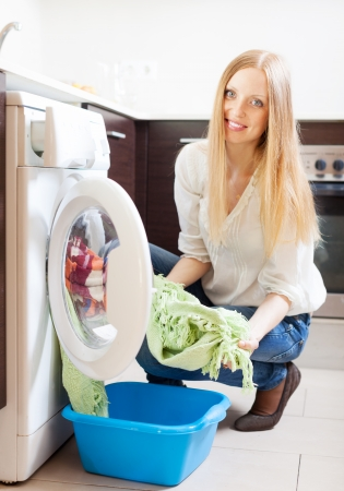 Home laundry. Happy long-haired woman loading clothes into the washing machine   photo