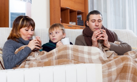 freezing family of three with cups of tea warming near warm radiator in home Banco de Imagens