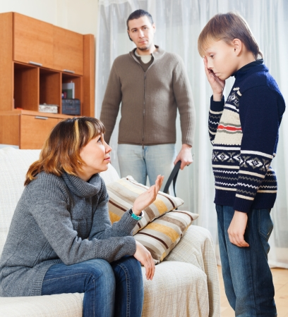 scandal: Mother and father scolding teenager boy at living room Stock Photo
