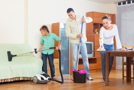 Happy couple with teenager son cleaning in living room photo