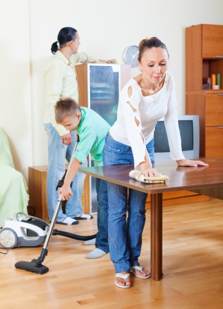home appliances: Ordinary family of three doing house cleaning with  cleaning equipment in  room