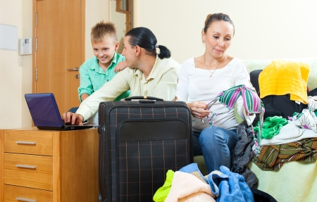 Ordinary family of three with luggage choosing the tickets on the internet in home going on holiday photo