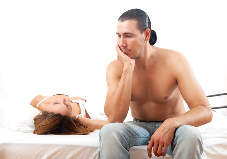 Sad man with problem in bed infront of his wife in bedroom photo