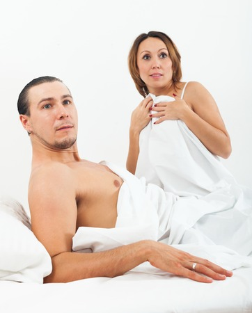 Middle-aged loving couple caught during adultery in bed photo