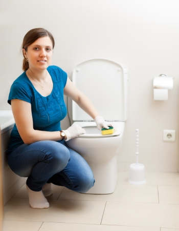 Smiling  woman cleaning toilet seat with sponge  photo