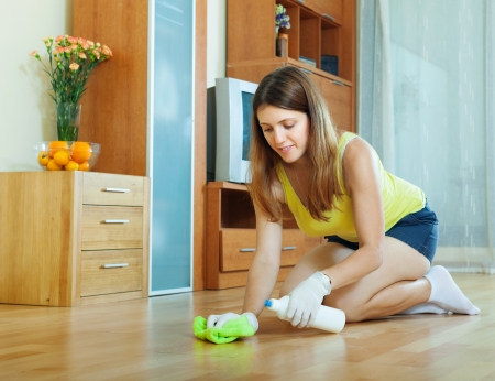 cleanser: woman rubbing wooden floor with rag and cleanser