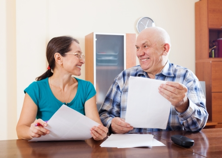 Happy mature couple holding financial documents at home   photo