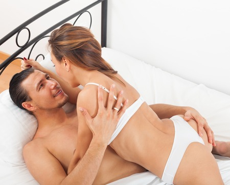 lovers kissing: Smiling lovers kissing and playing in bed at home Stock Photo