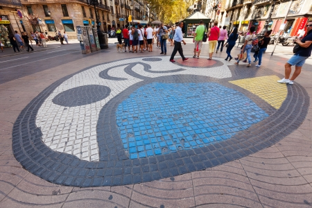 BARCELONA, SPAIN - SEPTEMBER 12: Walking people  at La Rambla on September 12, 2013 in Barcelona, Spain. Pavement mosaic by Joan Miro on la Rambla