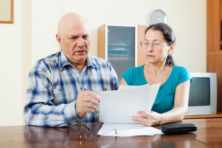 serious senior man with pensive mature woman fills in questionnaire  photo