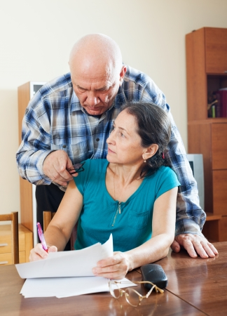 serious elderly man with wife reading financial documents at table Stock Photo