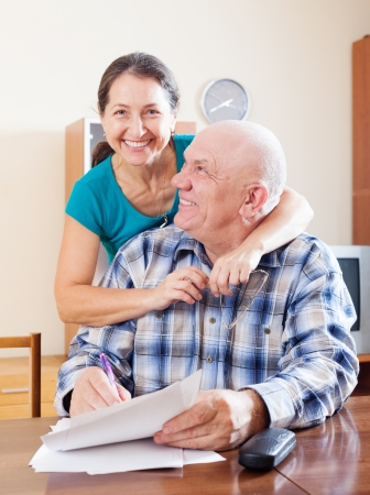 old people reading: happy mature couple fills in paper questionnaire together Stock Photo