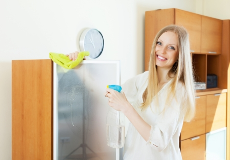 Positive  housewife cleaning  glass at home photo