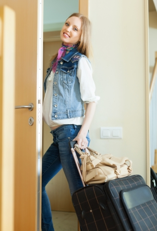 Long-haired positive woman with luggage leaving her home photo
