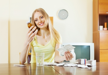 depressant: blonde woman with medications at table in living room