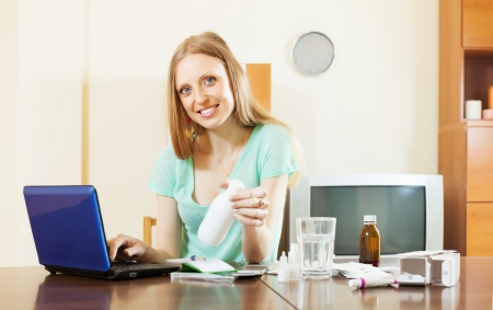 troche: Blonde long-haired woman choosing medication in online pharmacy at home