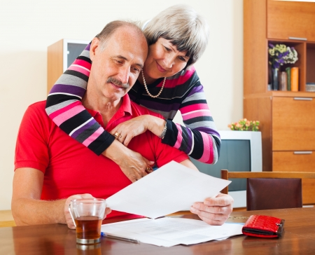 serious mature couple looking financial document at home interior photo