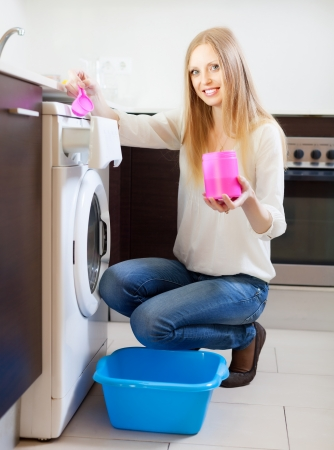 Long-haired woman doing laundry with detergent at home photo