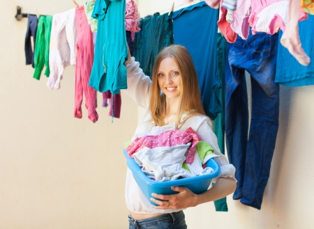 Smiling woman hanging clothes to dry on clothes-line photo