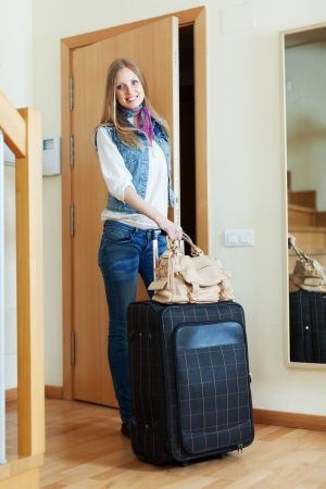 pensive positive woman with suitcase near door at home photo