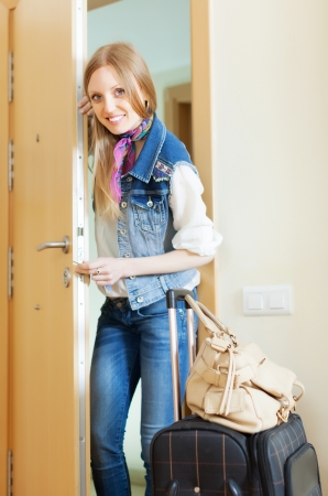 positive blonde woman with luggage in home Stock Photo