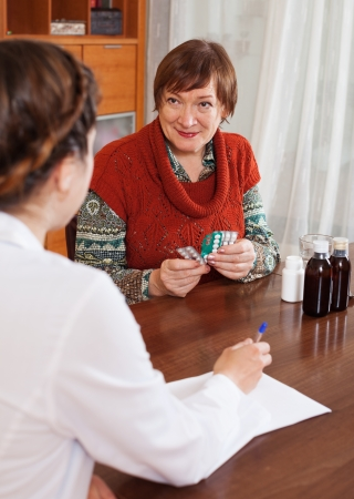 malaise: Mature woman speaking the doctor the symptoms of malaise at table. Focus on patient