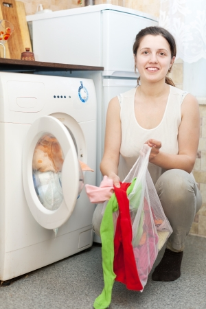 housewife in white with laundry bag  near washing machine   photo