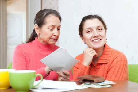 calculated: Adult daughter and mother is calculated the family budget at  home Stock Photo