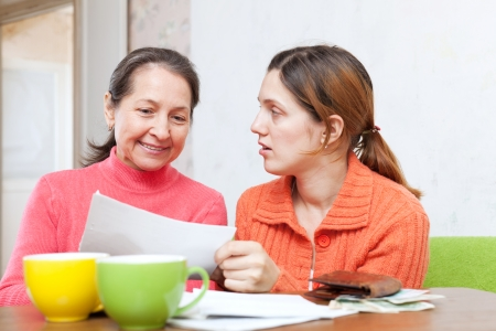utility payments: mother berates adult daughter for utility payments bills or credits. Focus on mature