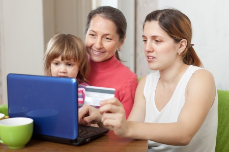 Happy family of three generations shopping online in living room at home photo