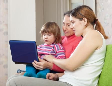 three generations of women:   Happy women  of three generations with laptop on sofa