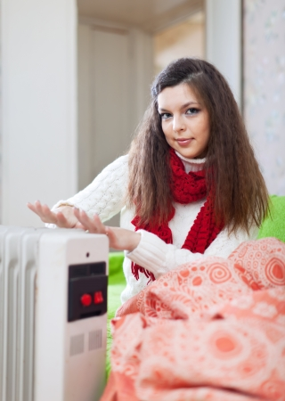 Girl warm  hands near radiator at home
