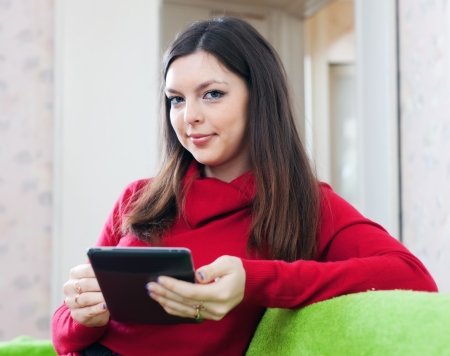 Girl in red uses tablet computer or electronic book t home photo