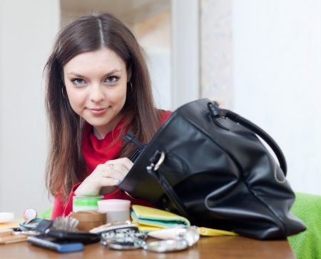 preoccupation: Girl looking for something in her purse at table in home