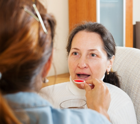 woman giving the cough syrup to mature mother at home photo